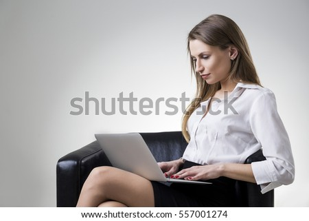 Side view of a beautiful businesswoman in a white blouse sitting in a leather armchair with her laptop.