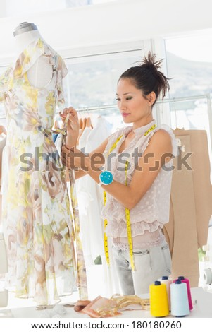 Side view of a beautiful female fashion designer working on dress at the studio - stock photo