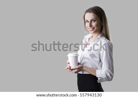 Side view of a beautiful smiling businesswoman wearing a white blouse and holding her paper cup of coffee. Mock up