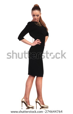 Side view of a beautiful young business woman looking down while holding her hands on the waist. - stock photo