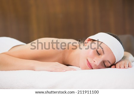 Side view of a beautiful young woman lying on massage table at spa center