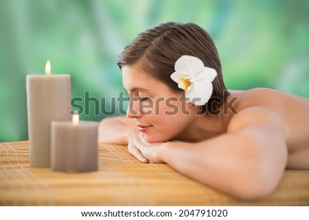 Side view of a beautiful young woman on massage table at health farm - stock photo