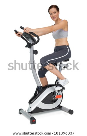 Side view of a beautiful young woman on stationary bike over white background