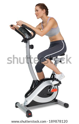 Side view of a beautiful young woman on stationary bike over white background - stock photo