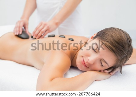 Side view of a beautiful young woman receiving stone massage at spa center