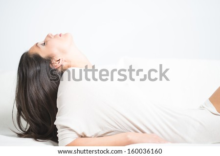 Side view of a beautiful young woman reclining on a sofa with her head tilted back and her long brunette hair dangling down behind her as she relaxes daydreaming at home - stock photo