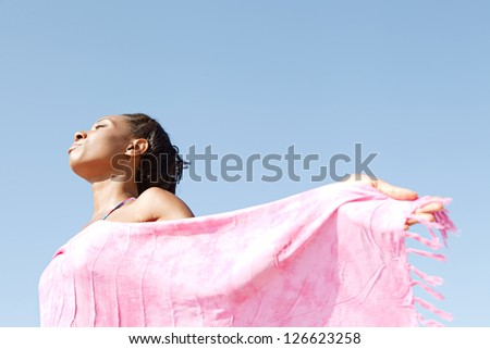 Side view of a black woman breathing fresh air on the beach and holding a pink sarong around her body, standing against a deep blue sky. - stock photo