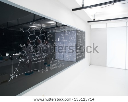 side view of a blackboard with formulas in a chemistry lab - stock photo