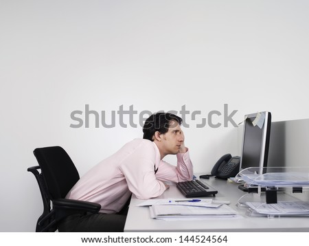 Side view of a bored male office worker looking at notes on computer monitor at desk - stock photo