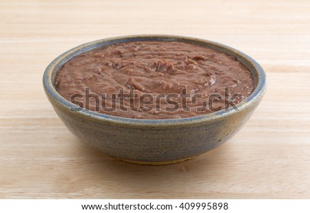 Side view of a bowl filled with black bean dip atop a wood table top.