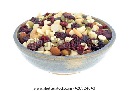 Side view of a bowl full of an assortment of nuts and dried cranberries trail mix isolated on a white background.