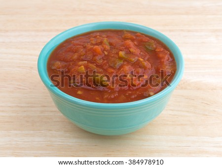 Side view of a bowl of chunky spicy salsa sauce on a wood background illuminated with natural light. - stock photo
