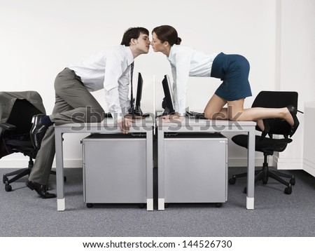 Side view of a business couple kissing over desks in the office - stock photo
