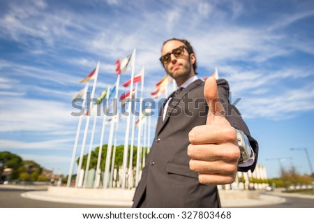 Side view of a business man outside in front of the flags making the ok gesture - Caucasian people - business, people and lifestyle concept - stock photo