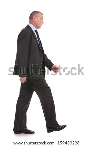 side view of a business man walking forward and looking away from the camera. on a white background - stock photo
