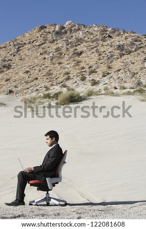 Side view of a business man working on laptop in desert - stock photo