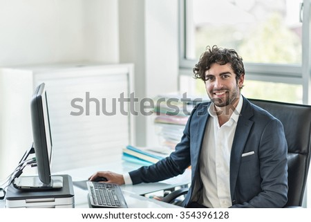 Side view of a business partner sitting at his tidy glass desk in a white office with large windows He has a beard and is wearing a dark suit with shirt He is answering his emails on his computer - stock photo