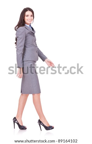 side view of a business woman walking in full length on white background - stock photo