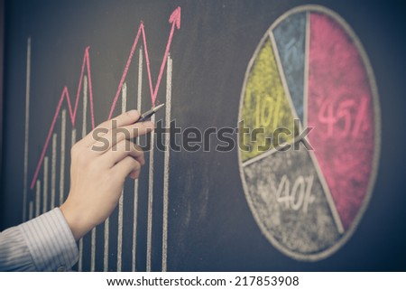 Side view of a businessman's hand. Business graph on a blackboard. - stock photo