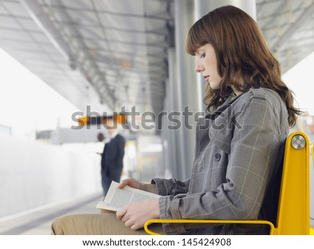 Side view of a businesswoman reading a book at train station bench - stock photo