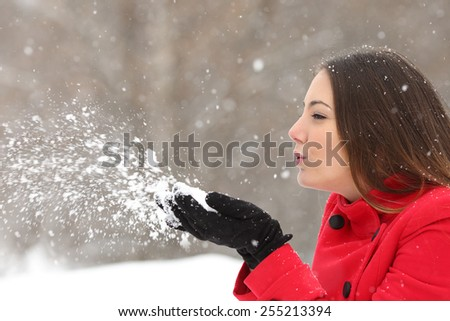 Side view of a candid woman in red blowing snow in winter during a snowfall - stock photo
