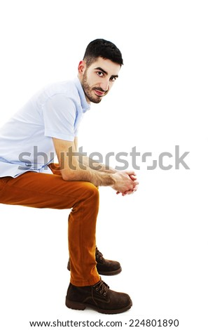 Side view of a casual fashion man sitting on white background and looking at camera  - stock photo