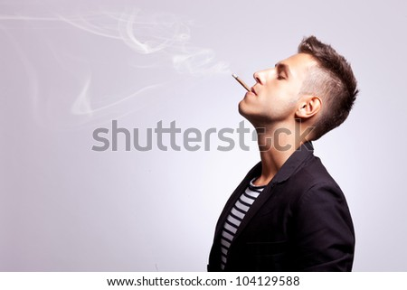 side view of a casual fashion man smoking a cigar on gray background - stock photo
