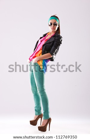 side view of a casual fashion woman in leather jacket and sunglasses standing with her hands in her pockets - stock photo