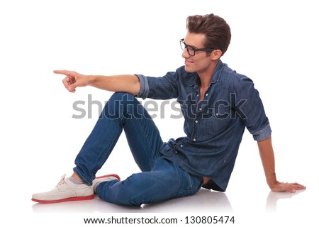 side view of a casual young man sitting on the floor and pointing and looking to the side of the camera, while smiling. isolated on white - stock photo