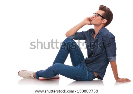side view of a casual young man sitting on the floor and speaking on th phone while looking away from the camera. isolated on white - stock photo