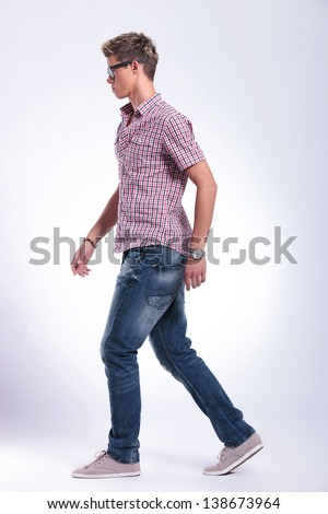 side view of a casual young man walking forward, away from the camera. on gray background - stock photo
