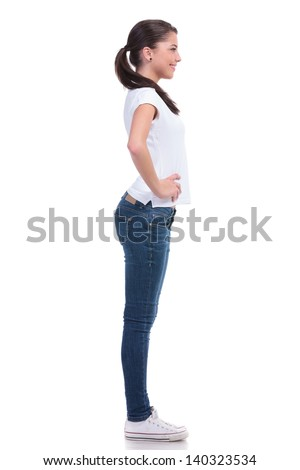 side view of a casual young woman standing with her hands on her hips and smiling while looking away from the camera. isolated on white background - stock photo