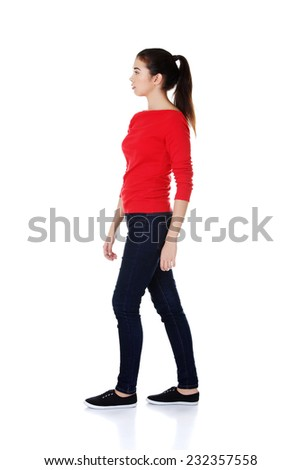Side view of a casual young woman walking. - stock photo