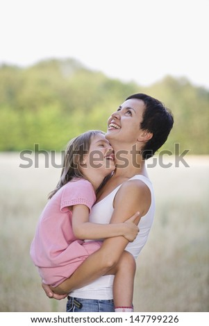 Side view of a cheerful mother carrying daughter in the blurred field