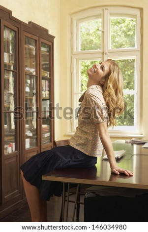 Side view of a cheerful young woman sitting on table in living room with head thrown back - stock photo