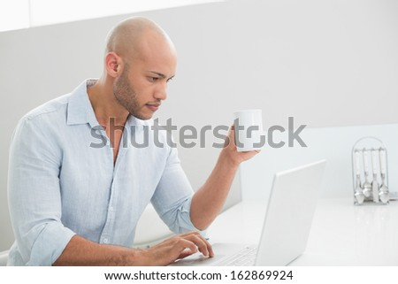 Side view of a concentrated casual young man using laptop at home