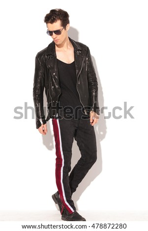 side view of a cool rocker man in leather jacket and sunglasses walking in studio