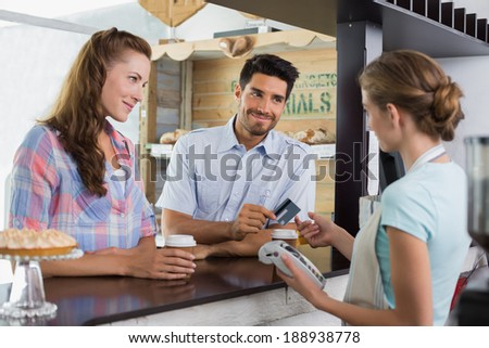 Side view of a couple paying bill at coffee shop using card bill - stock photo