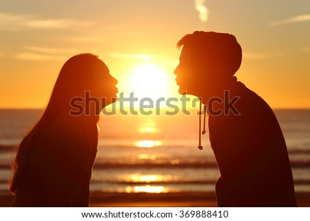 Side view of a couple silhouette of teenagers kissing the sun with love at sunset on the beach with the horizon in the background - stock photo