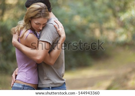 Side view of a couple standing on forest trail and hugging - stock photo