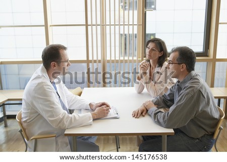 Side view of a doctor conversing with a couple at hospital desk - stock photo