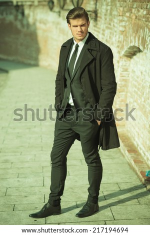 Side view of a elegant business man on a sidewalk with his hand in pocket, looking at the camera. Vintage look. - stock photo