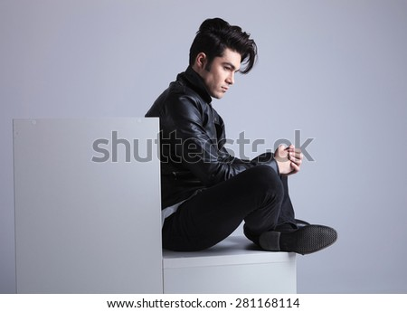 Side view of a fashion man sitting on a while furniture while looking away from the camera with his hands together. - stock photo