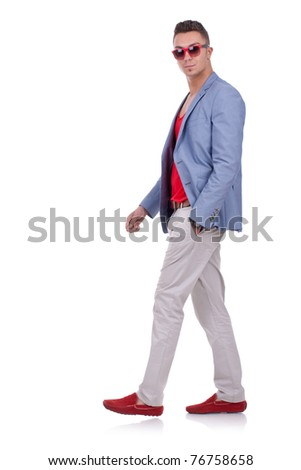 side view of a fashion man walking and looking at the camera - stock photo