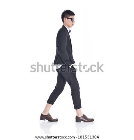 side view of a fashion man walking forward - stock photo