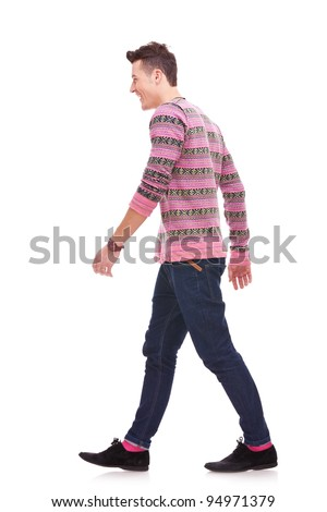 side view of a fashion man walking forward over white . young casual man walking from right to the left of the camera - stock photo
