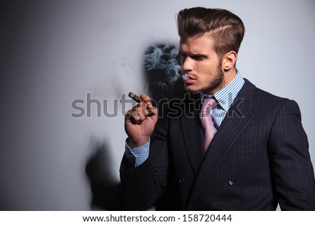 side view of a fashion model in suit and tie enjoying his cigar on gray background - stock photo