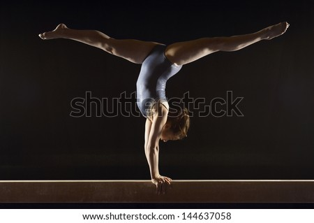 Side view of a female gymnast doing split handstand on balance beam against black background - stock photo