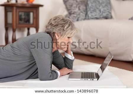 Side view of a female pensioner using laptop in living room at home - stock photo