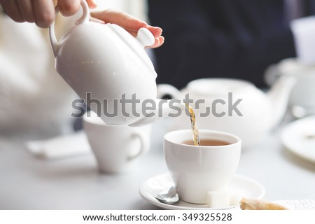 side view of a female pouring tea - stock photo